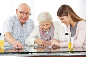 24321876 - a young social worker solving jigsaw puzzle with senior couple at home